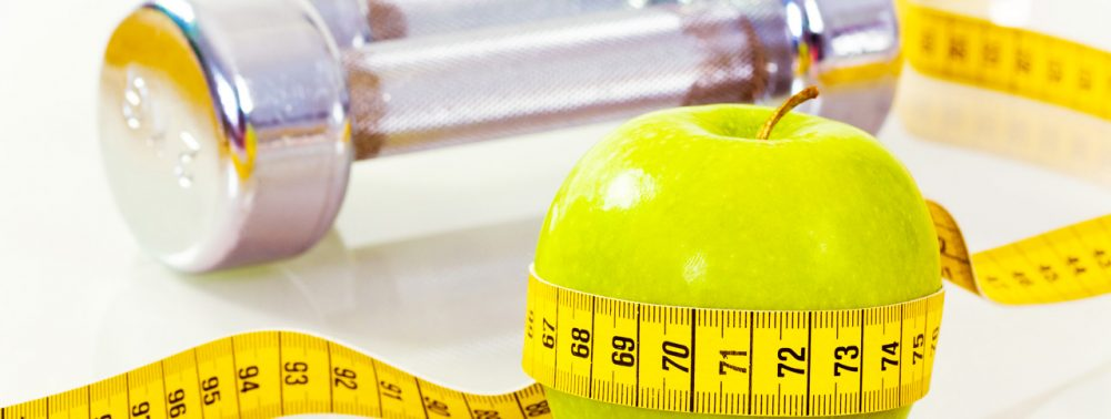 Apple and weight representing fitness and healthy nutrition
