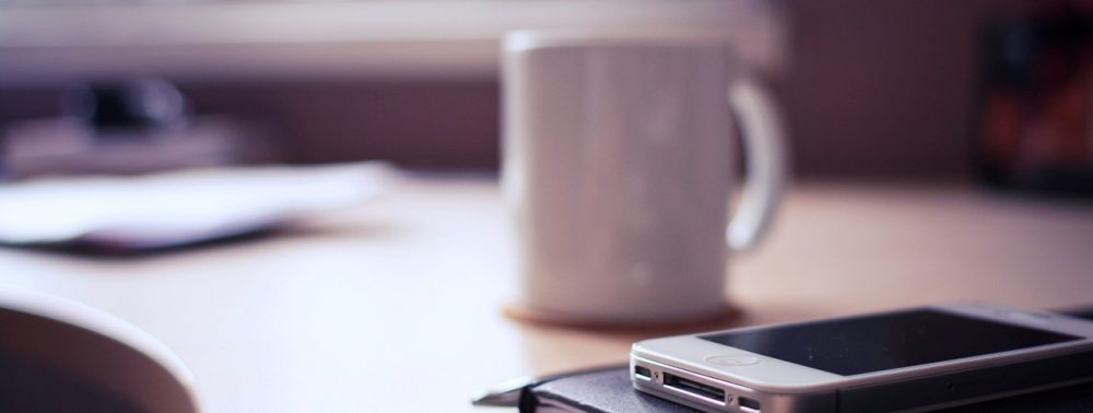 office table with mobile phone and coffee